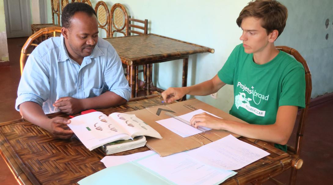A Projects Abroad volunteer pointing out what different things are as part of his French lesson in Madagascar